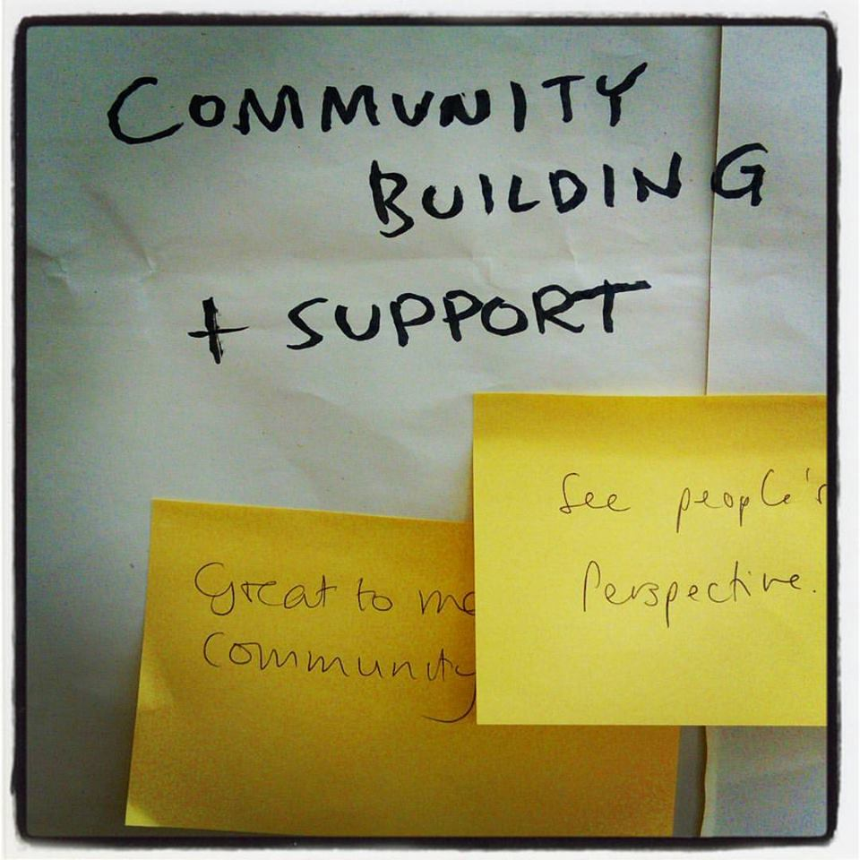 Picture of post-it notes with words community building and support behind
