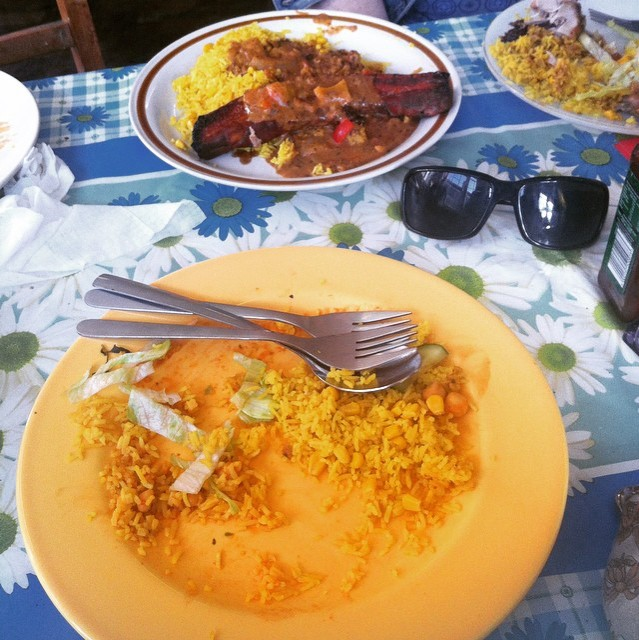 Picture shows a plate with some rice on and behind another plate with more food