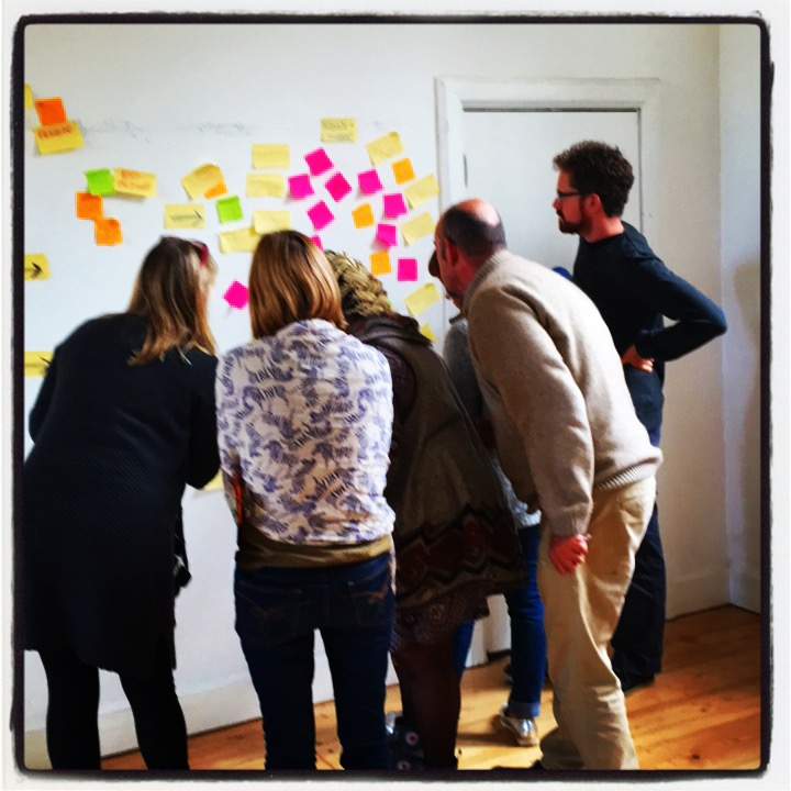 A group of people, backs to the camera, reading post-it notes displayed on a wall