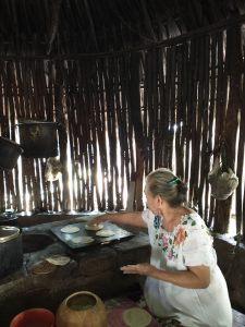 Maya woman using masa (dough made from crushing and kneading maize seeds) to make handmade tortillas in a traditional Mayan kitchen - by Karla G. Hernandez-Aguilar