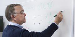 Prof. Murray Lark wearing blue jumper drawing on whiteboard with marker pen