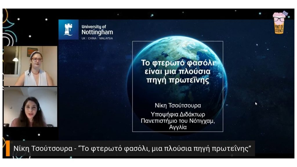 A presentation slide with a globe and writing in Greek. To the left are two people, the speaker and the organiser.