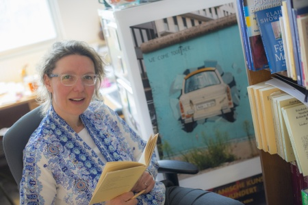 Heike sits in a chair with a book open in front of her, but looking at the camera. She is dressed in a blue shawl and has clear-framed glasses on