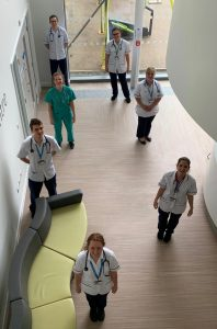 A group of seven physiotherapy staff social distancing in the entrance to a clinical building