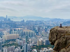 Physiotherapy graduate overlooking a city from the top of a cliff in Hong Kong