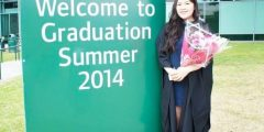 Physiotherapy graduate holding a bouquet of flowers next to a 'Welcome to Graduation Summer 2014' sign