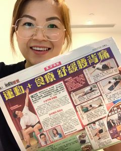 Physiotherapy graduate, Angela, holding up her article from a national newspaper in Hong Kong