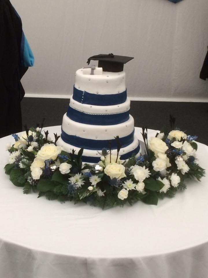 Four-tier cake with blue ribbon surrounded by flowers with a mortar board and degree certificate on top