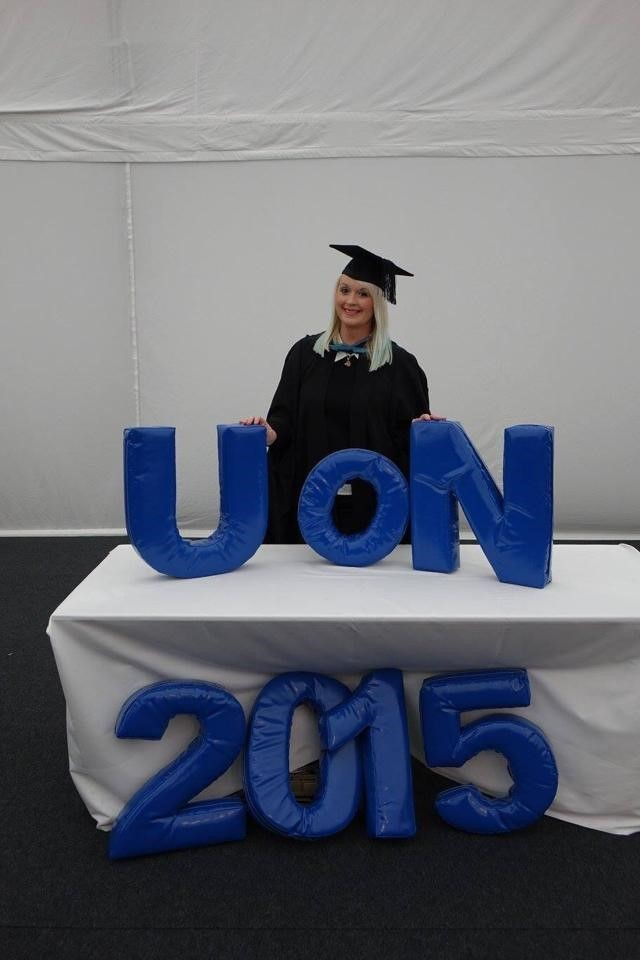 Stephanie Manning in cap and gown behind big letters reading UoN 2015