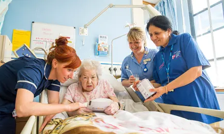 Group of nurses including Liz Charalambous caring for an elderly patient in a hospital bed