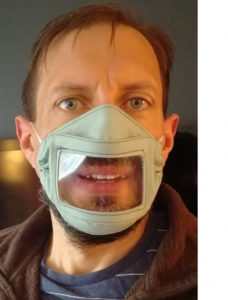 Photo showing man wearing a mask with a clear section, showing the mouth