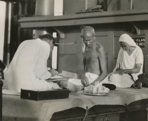 Photo depicting Mirabehn and another secretary taking dictation from MK Gandhi in the covered hold of the S.S. Rajputana, which Gandhi used as his quarters