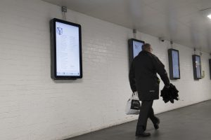 Poetry in Nottingham Public Places , man walking past display screens