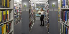 Girl reading book between book stacks in GGL