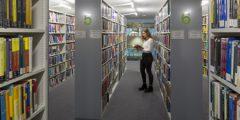 Girl reading book between book stacks in GGL