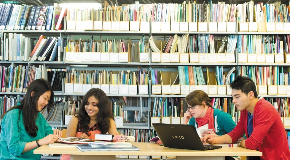 Four students sitting in the library in front of books