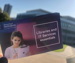 A copy of the Libraries and IT Services essentials guide with George Green Library in the background