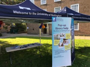 Library stall outside Cripps Hall on a bright day