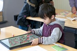 A young boy plays 'The Silver Bullet' game at Mayfest 2014.