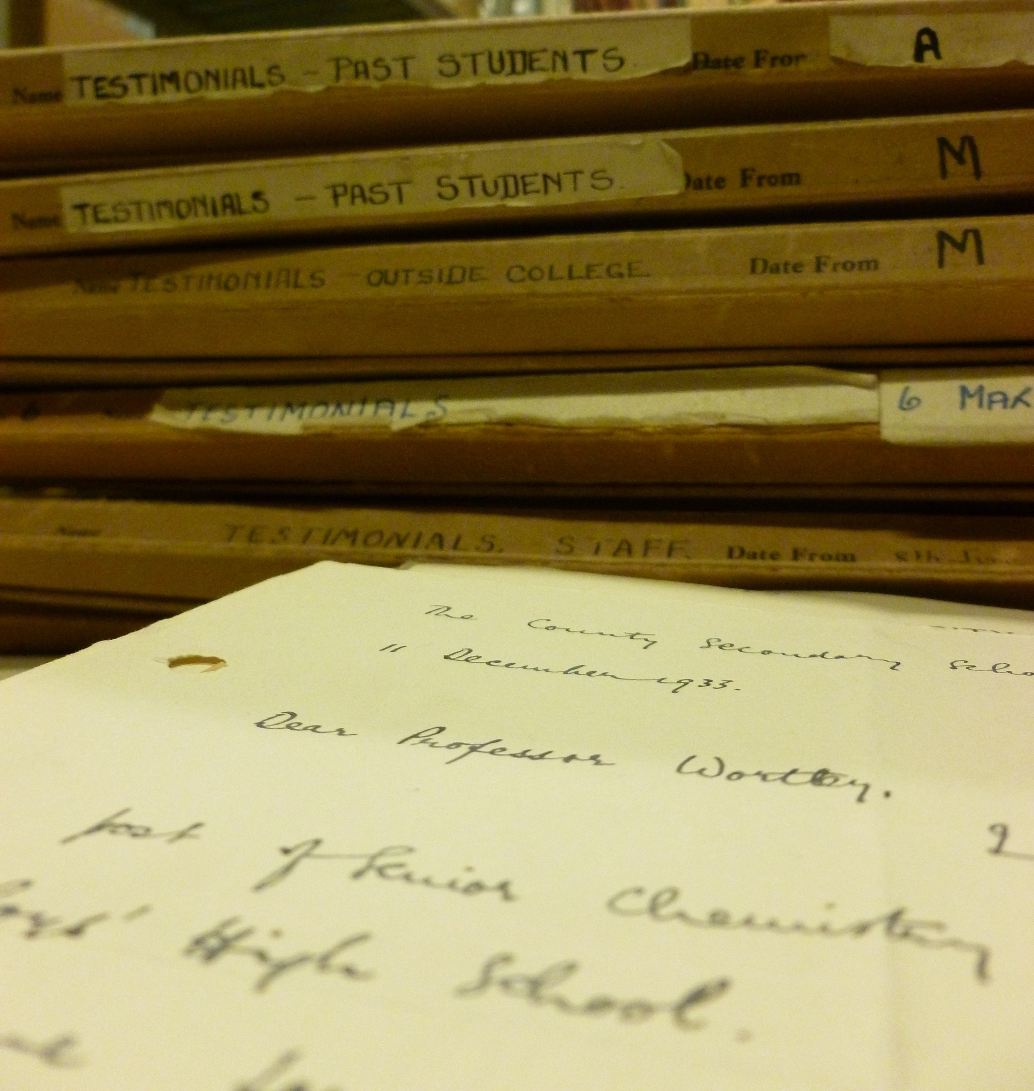 A stack of folders of UCN Testimonials from the 1930s