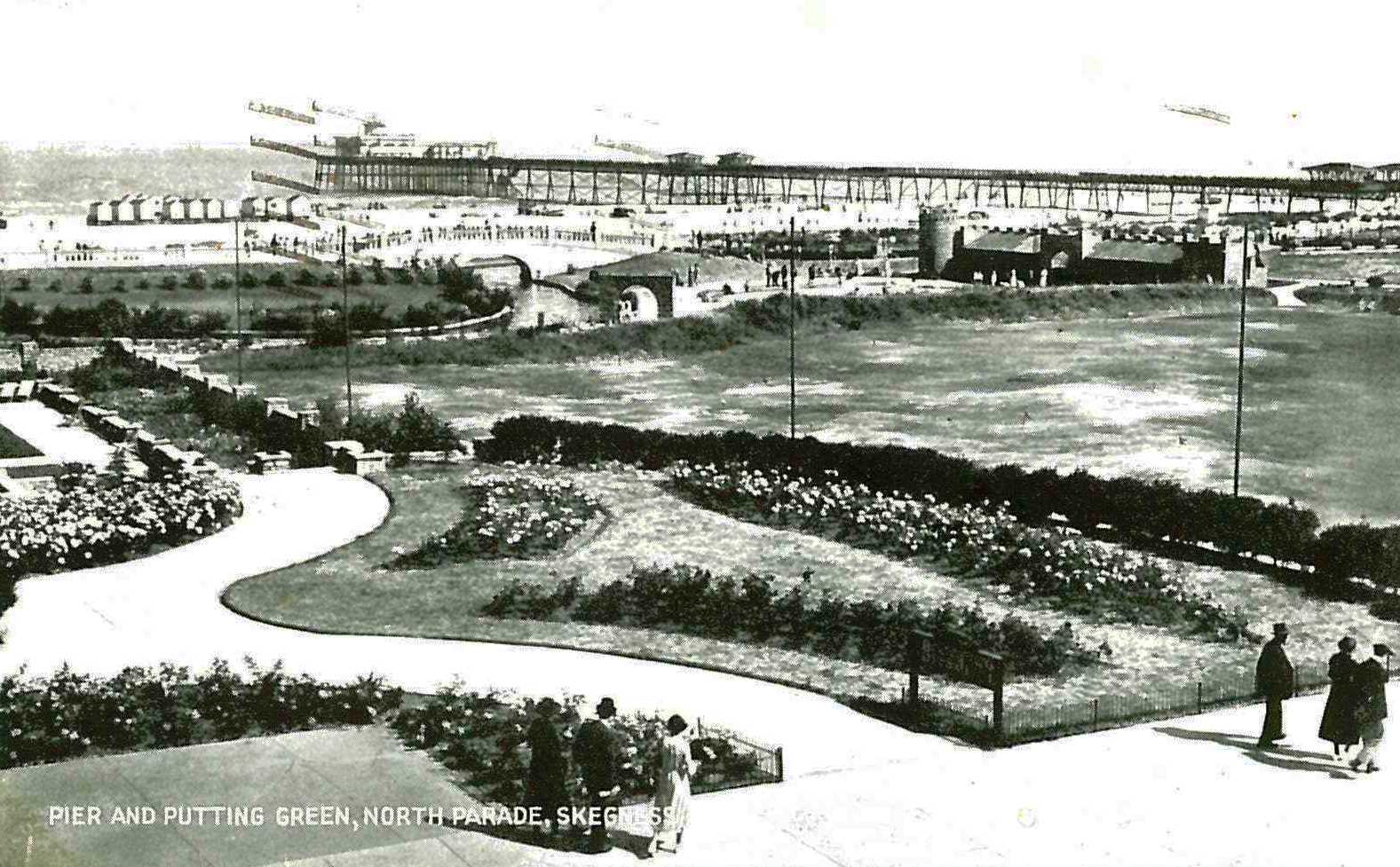 Black and white postcard of the putting green at Skegness, with the pier in the background, c.1938 (Ref: MS 192/117)