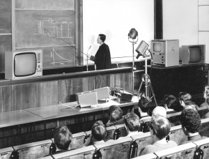 Shows the lecturer, dressed in a black gown, pointing at a diagram on the blackboard; also shows various electrical equipment, and the first 3 rows of students.