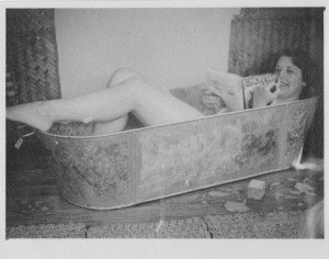 Student in the bath reading the Student Union rag mag 'Chickerah', c.1950; MS 292/1/101