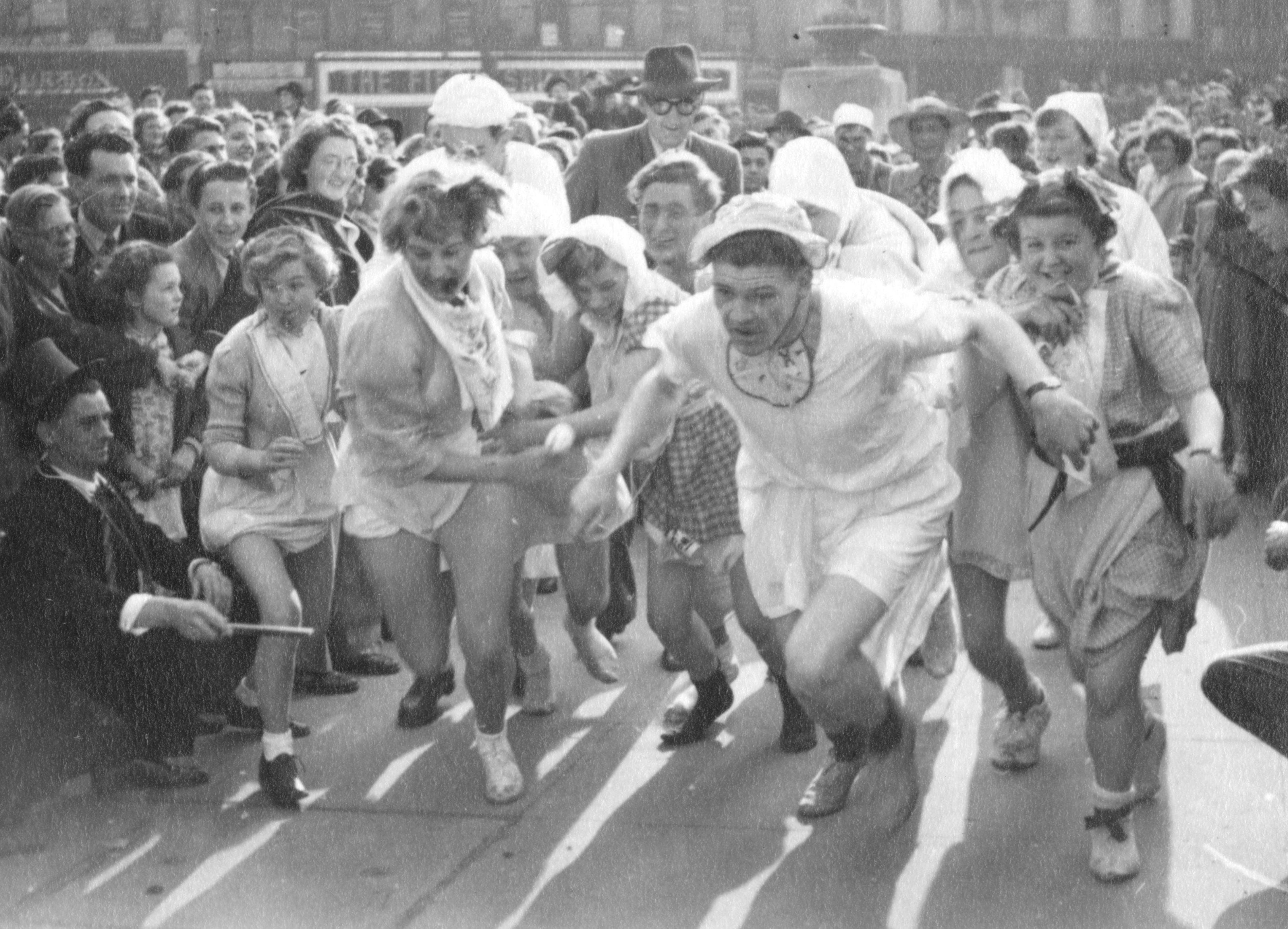 Students running in a fancy dress race, 1950