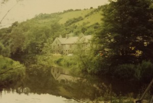 Colour photo of Litton Mill with hills in the background and the river in the foreground