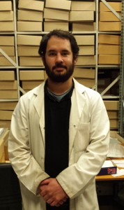 Matt dressed in his white coat, standing in front of shelves of boxes in the archives store