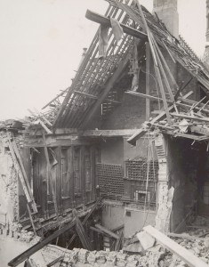Close up of exposed timber roof beams and a collapsed floor caused by bomb damage