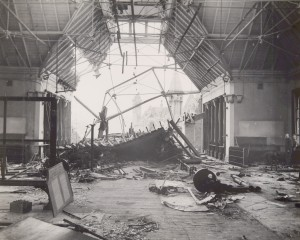 Photograph of the interior of the bomb damaged building looking out through the massive hole where the wall and roof were blown out