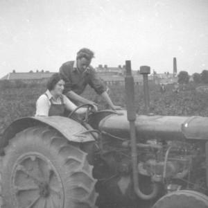 One male and one female student on a tractor, c.1948-1950