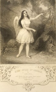 Image of an actress playing Ariel, posed against the backdrop of a garden, with wings and wearing a white dress