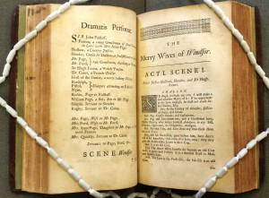 Photo of the printed volume open at The Merry Wives of Windsor and held open with snake weights