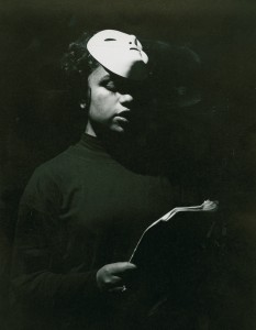 Black and white photograph of a Slavonic Studies student production of 'The Nose',  showing the actress reading a script with her white mask pulled up to her head, 1980s
