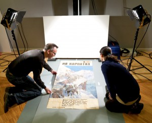 Two members of digitisation staff laying out 5 feet long poster surrounded by lights and camera equipment