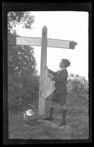 Photo of a young boy holding a map and looking at a blank signpost at a crossroad, MS 565/120