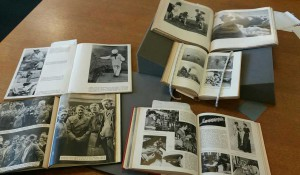 Various German books spread on a table and on foam book supports, all opened to pages of black and white photos