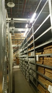 Photo looking down an aisle in the Store showing metal shelves with leather bound volumes.