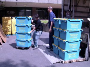 Men moving plastic blue crates into a lorry outside Hallward Library