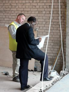 Two men holding plans for building Conservation.