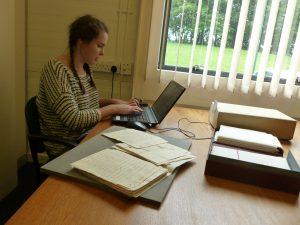 Photo of Megan working on a laptop and boxes of documents in the Reading Room