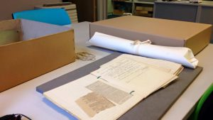 Photo of an archive box, a rolled up plan and a file of letters and newscuttings on a table