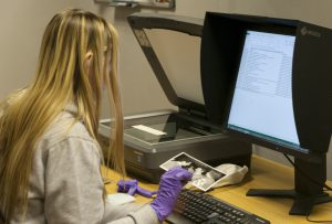 Isobel sitting at a scanner, wearing nitrile gloves, digitising photos of the University