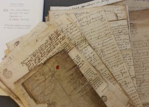 Bundle of handwritten documents arranged in a pile and photographed from above