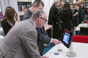 Two men scrolling through the iBook on a tablet in the Reading Room