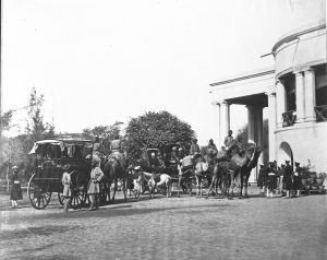 Black and white photo of Indian soldiers, horses and carriages outside a building