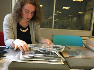 Photo of the volunteer sorting through photos in protective sleeves