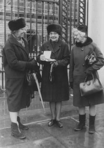 Black and white photo of the three women outside the railings, possibly at Buckingham Palace